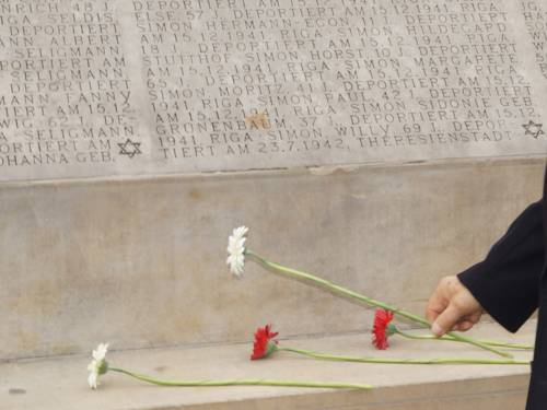 Two white and two red gerberas at the bottom of the Holocaust Memorial listing the names of the dead