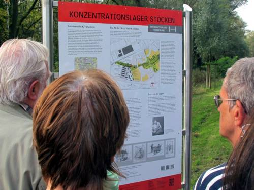 Teilnehmer einer Fahrradtour betrachten die Informationstafel zum KZ Stöcken, 2014.