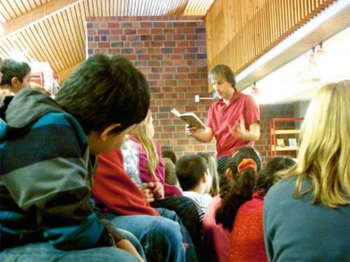 Ein Mann liest einer Schulklasse ausdrucksstark aus einem Buch vor