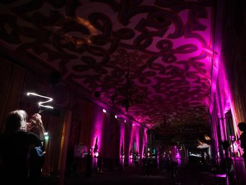 """Blick in die Galerie bei einer Vorstellung von """"Atlas – Inseln der Utopie"""", der Raum wird durch pinkes Licht erhellt"""