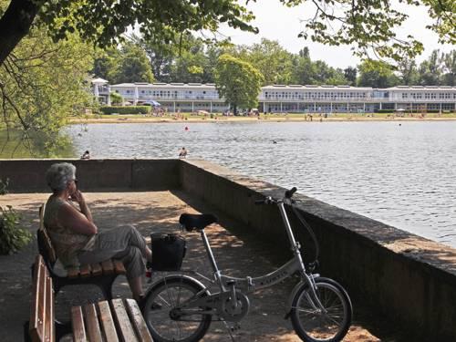 Eine ältere Dame sitzt auf einer Bank am Maschsee und schaut auf den See hinaus, neben ihr steht ein Fahrrad