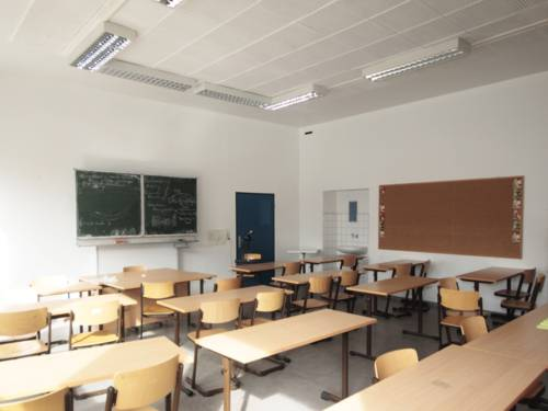 Blick in ein leeres Klassenzimmer an der Leibnizschule, zu sehen sind mehrere Tische und Stühle sowie eine beschriebene Tafel