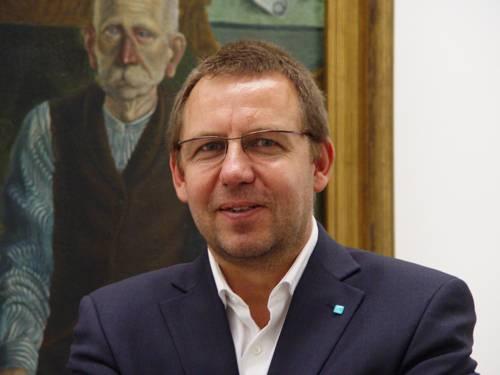 Portraitfoto von Dr. Reinhard Spieler vor einem Gemälde im Sprengel Museum Hannover
