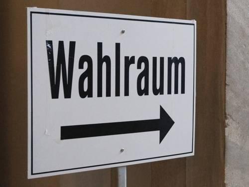 """Ein weißes Schild mit der Aufschrift """"Wahlraum"""" und einem nach rechts zeigenden Pfeil"""
