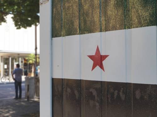 Die syrische Flagge, die auf einen Container gegenüber der Markthalle gemalt ist