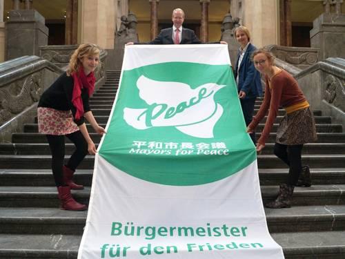Vier Personen präsentieren auf der Treppe in der Rathaushalle die grün-weiße Flagge der Mayors for Peace