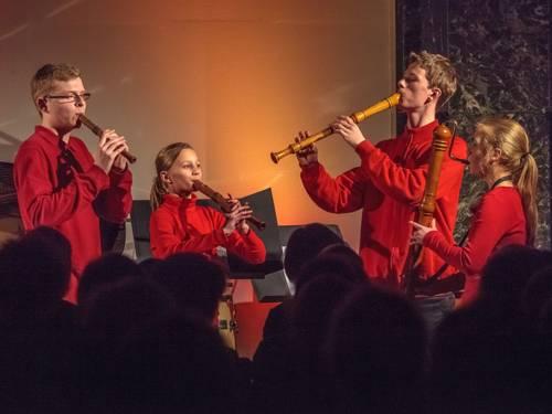 Vier junge Menschen spielen als Blockflötenquartett vor einem Publikum