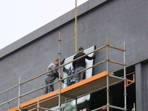 Zwei Arbeiter platzieren ein Fensterglas an der Westloggia des Erweiterungsbaus des Sprengel Museums