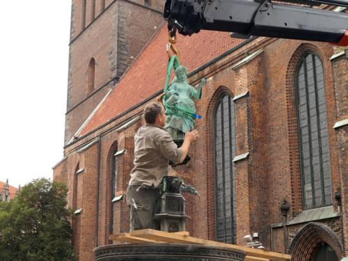 Ein Mitarbeiter der Stadt steht im Brunnen und achtet darauf, dass die an einem Kran schwebende Frauenfigur keinen Schaden nimmt