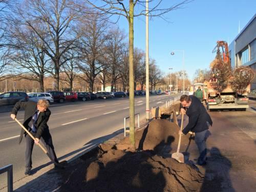 Harald Härke und Reinhard Spieler schaufeln ein wenig Erde beiseite, um die Pflanzung einer Linde vorzubereiten