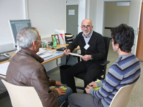 Ein Sozialarbeiter im Gespräch mit zwei Flüchtlingen
