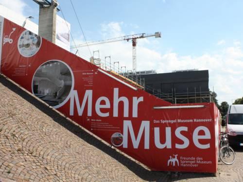Der Bauzaun am Sprengel Museum mit Baukran und dem dunklen quaderförmigen Erweiterungsbau im Hintergrund
