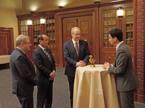 Vier Männer, die um einen runden Tisch stehen, auf der eine goldene Friedenstaube steht.