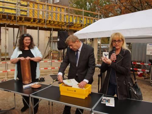 Zwei Frauen und ein Mann befinden sich auf einer Baustelle und befüllen eine Zeitkapsel mit alltäglichen Gegenständen.