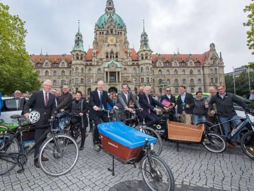 Menschen mit Fahrrädern und Elektroautos.