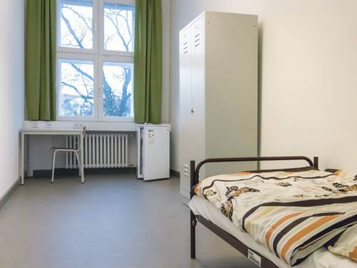Zimmer mit einem Bett, einem Schrank, einem Tisch und einem Stuhl.