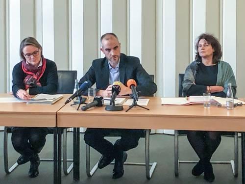 Drei Personen sitzend an einem Tisch während einer Pressekonferenz