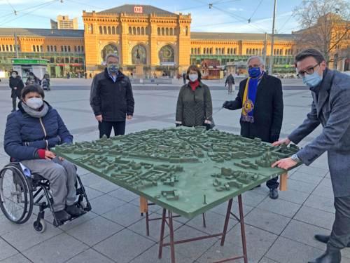 Fünf Personen um ein großes Stadtmodell. Alle halten Abstand und tragen einen Mund-Nasen-Schutz.