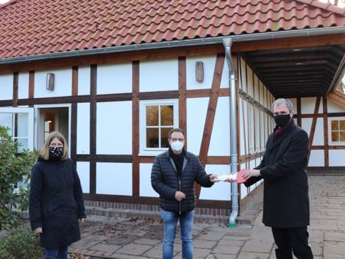 Drei Personen vor einem Fachwerkhaus in einem Park. Ein Herr übergibt einem anderen einen Schlüssel.