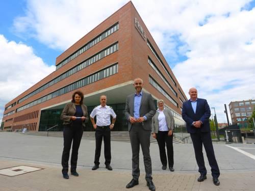 Fünf Personen vor einem Gebäude.