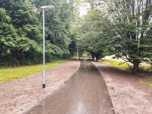 Ein asphaltierter Weg durch einen Grünzug