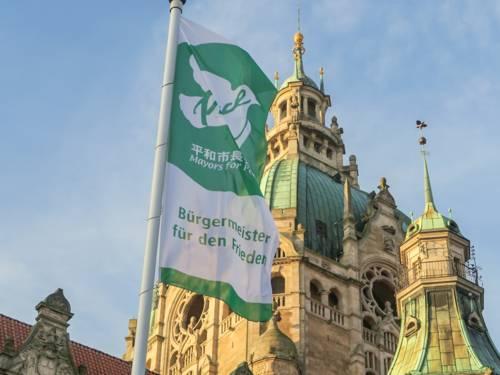 Die Flagge der Mayors for Peace weht vor dem Neuen Rathaus
