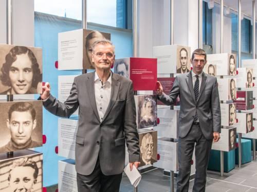 Zwei Männer stehen an zwei Säulen, auf denen Porträtfotos von anderen Menschen zu sehen sind