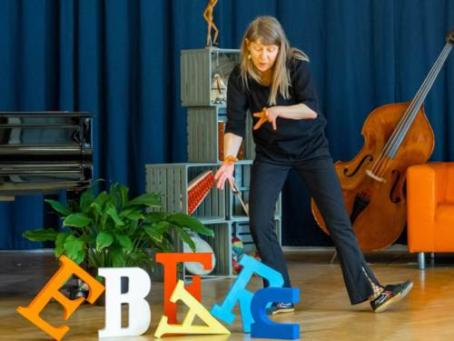 Eine Frau zwischen Buchstaben und Instrumenten.