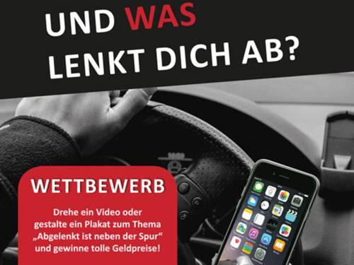 Nahaufnahme eines Autolenkrads und einer Hand, die ein Handy bedient, statt den Wagen zu lenken.