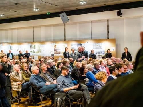 Viele Personen in einem Saal - sitzend und stehend.