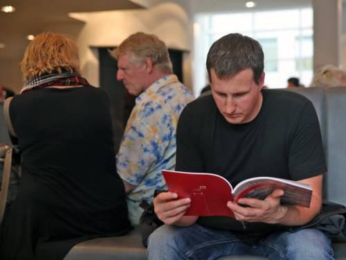 Ein junger Mann liest in einer Broschüre.