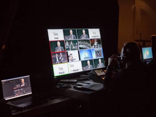 Symbolbild für ein LiveStream. Ein Bildregisseur sitzt vor einem großen Monitor und stellt die Livebilder der Übertragung zusammen.