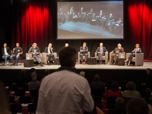 Ein Veranstaltungsbesucher richtet eine Frage an die Fachleute auf dem Podium