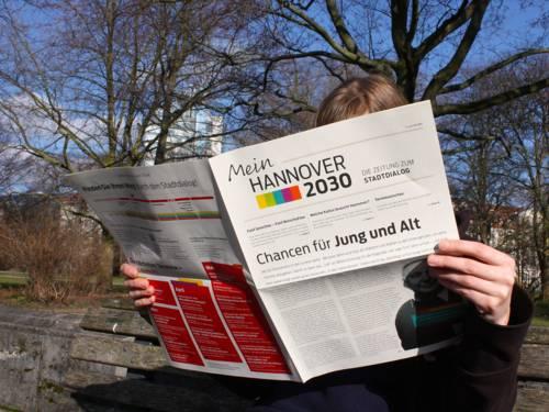 Ein junge Frau sitzt auf einer Parkbank und liest in einer Zeitung