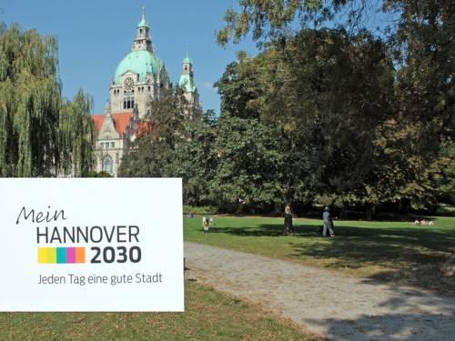 """Bilck auf das Rathaus. Im Vordergund das Logo vom Stadtdialog """"Mein Hannover 2030"""""""
