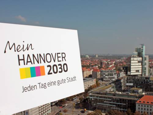 """Blick vom Rathausturm auf das Gebäude der Nord LB - im Vordergund das Logo vom Stadtdialog """"Mein Hannover 2030"""""""