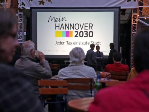 """Symbolbild für den liveStream- Menschen schauen auf einer Leinwand den Trailer """"Mein Hannover 2030"""""""