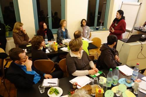 Eine Gruppe Erwachsener sitzt in einem Raum und hört einen Vortrag