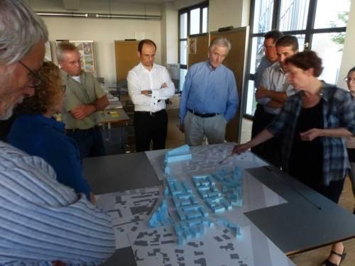Mehrere Personen, vor einem Tisch mit Modellentwurfen stehend