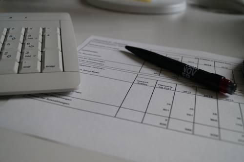Bildausschnitt eines Schreibtischs, auf dem sich eine PC-Tastatur, ein Kugelschreiber und ein bedrucktes Blatt Paier befinden.
