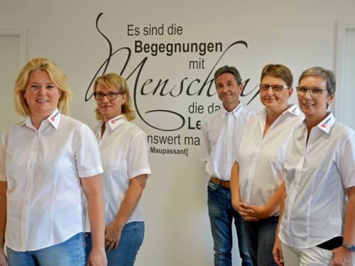 """Vier Frauen und ein Mann stehen vor einer Wand, auf der ein Zitat von Guy de Maupassant steht: """"Es sind die Begegnungen mit Menschen, die das Leben lebenswert machen""""."""