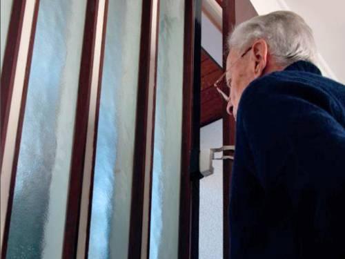 Ein Senior öffnet die Wohnungstür nur einen Spalt weit