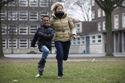 Eine Frau und ein Kind laufen fröhlich bei herbstlichen Wetter über eine Wiese.
