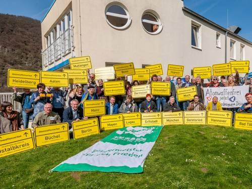 """Gruppenfoto: Mit symbolischen Ortsschildern mit der Aufschrift """"Atomwaffenverbot"""" zeigen Bürgermeisterinnen und Bürgermeister, Abgeordnete und Friedensaktivisten ihre Haltung für ein weltweites Atomwaffenverbot."""