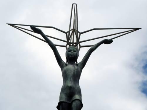 Die Statue eines Kindes mit ausgebreiteten Armen vor bewölktem Himmel.