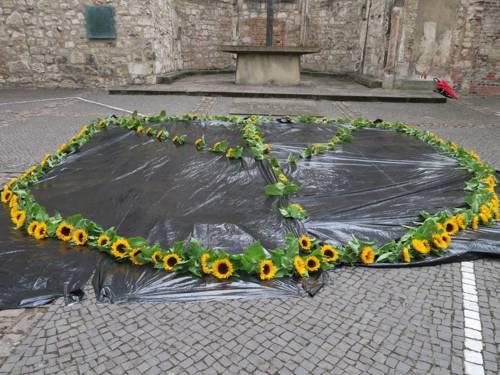 Im Innenhof der Ruine der Aegidienkirche liegen vor dem Altar Sonnenblumen in Form des Friedenszeichens.