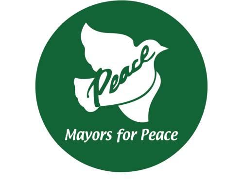 """Das Logo zeigt eine weiße Taube auf grünem Grund mit den Worten """"Mayors for Peace""""."""