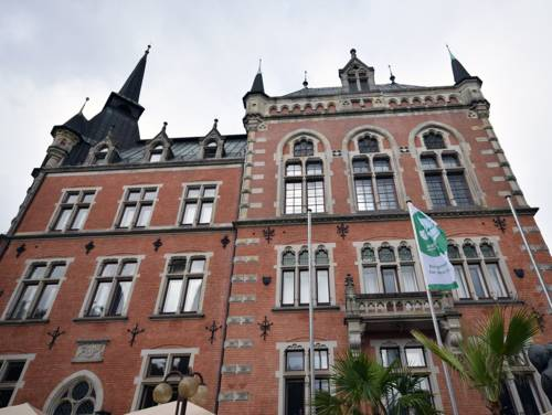Ein historisches Backsteingebäude, davor eine gehisste Mayors-for-Peace-Flagge