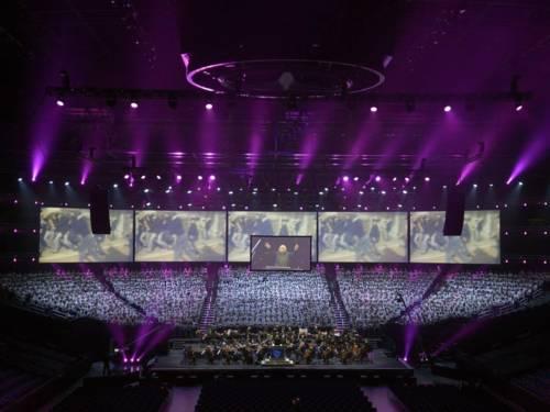 Ein Chor mit mehreren hundert Sänger*innen in einer großen Halle in violettem Licht.