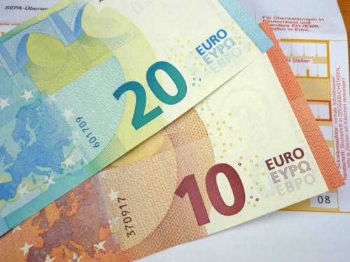 Ein Zwanzig-Euro-Schein und ein Zehn-Euro-Schein auf einem Überweisungsträger